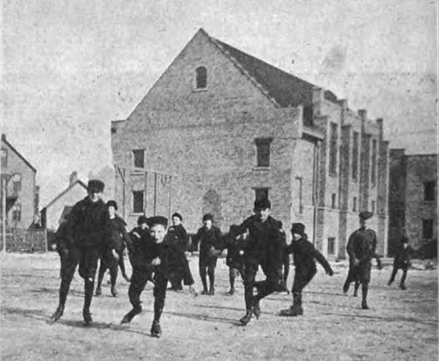 """Photograph of children playing at the University of Chicago Settlement, captioned """"Gymnasium of University Settlement."""" From page 388 of The Kindergarten Teacher, vol. 13, 1900-1901. Sourced from the Wikimedia Commons where it is said to be in the public domain."""